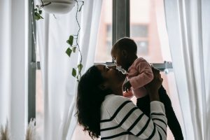 Mom holding baby in front of window learning about the child support updates in 2020 for NC