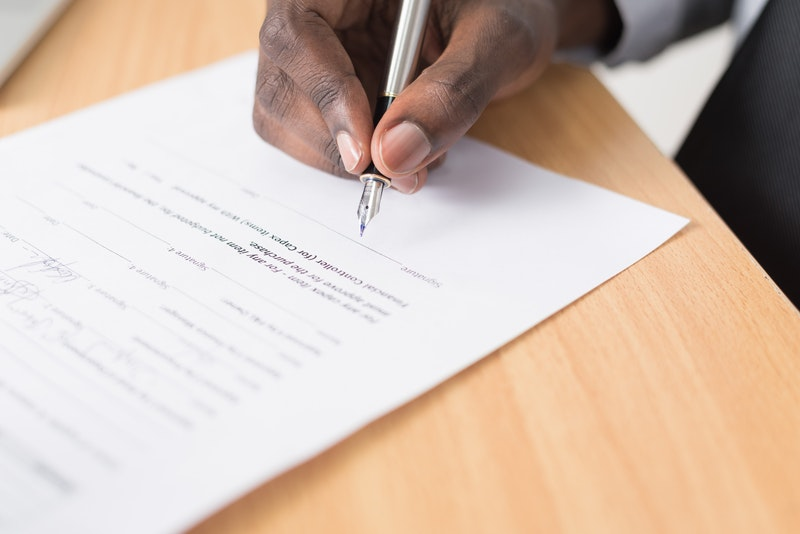 Man signings a postnuptial agreement with his family law attorney in Raleigh, NC
