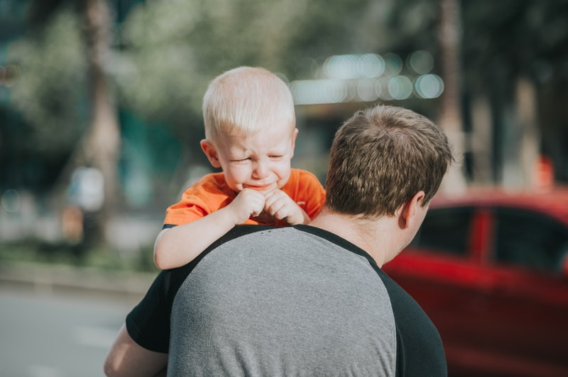 Father carrying son who is crying because of parental alienation of